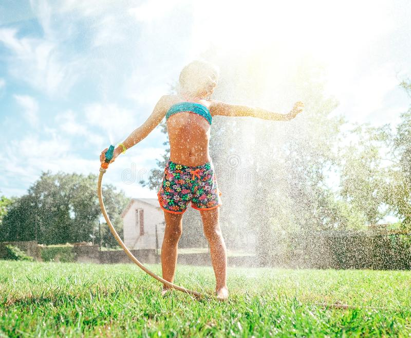 A menina bonito refresca-se da mangueira molhando do jardim imagens de stock royalty free