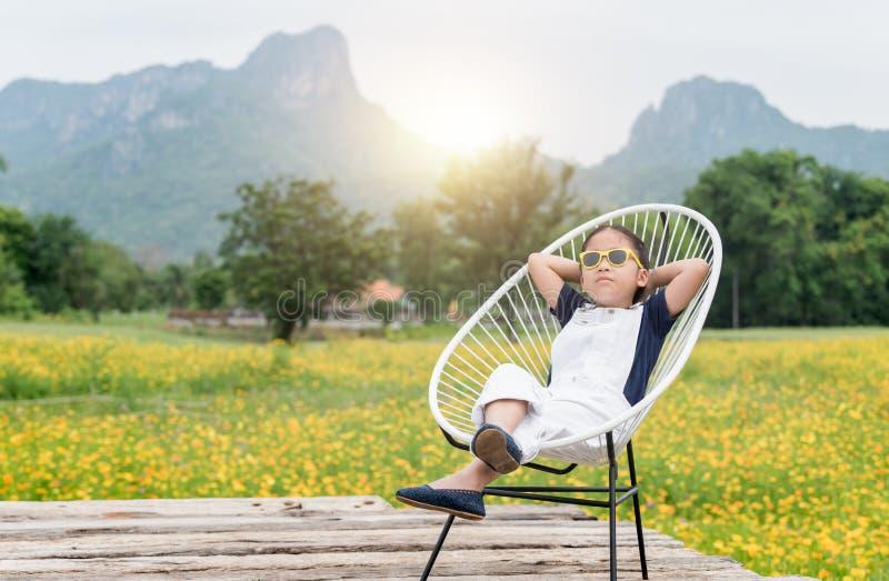 A menina bonito senta-se e relaxa-se na cadeira e no fundo amarelo da flor fotografia de stock