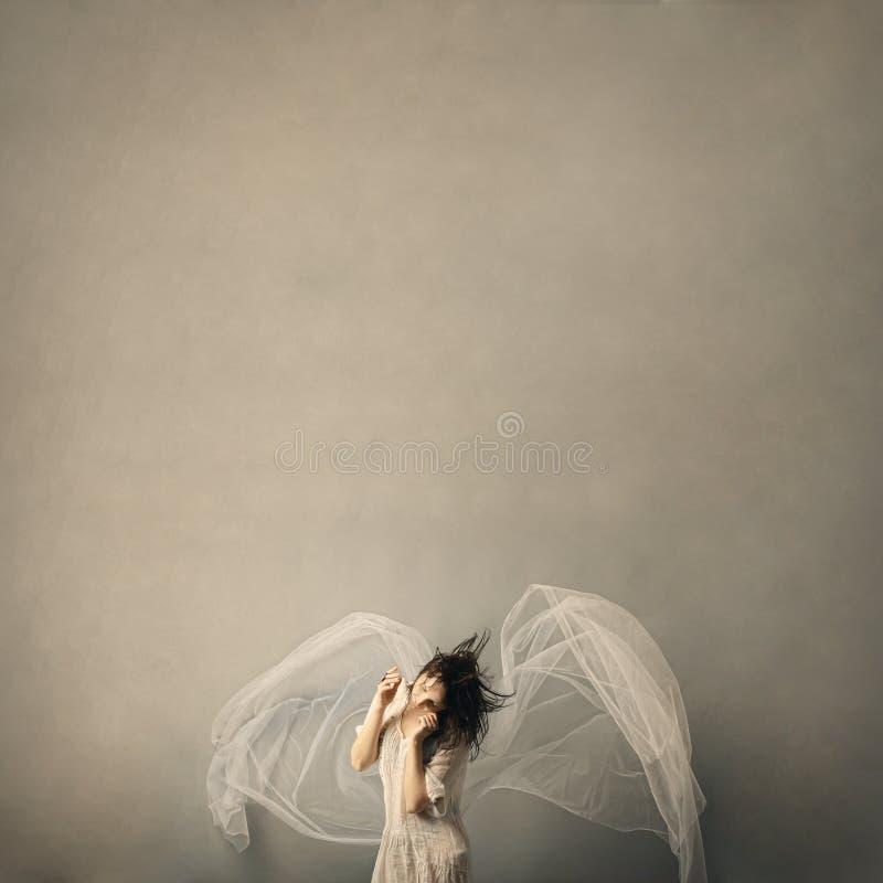 Menina bonito sob a forma de um anjo que levanta em um fundo cinzento fotos de stock