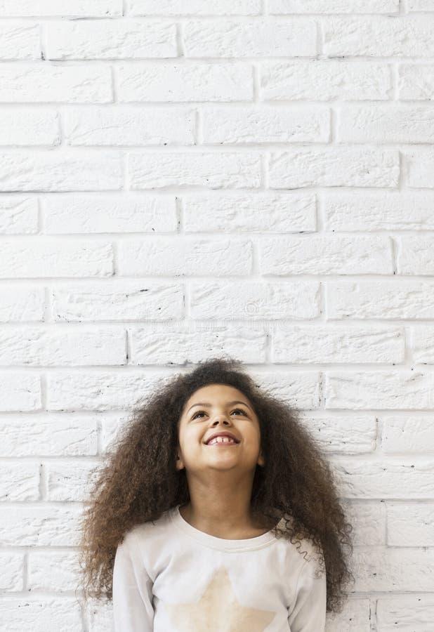 Menina bonito sobre uma parede de tijolo que olha acima fotografia de stock royalty free