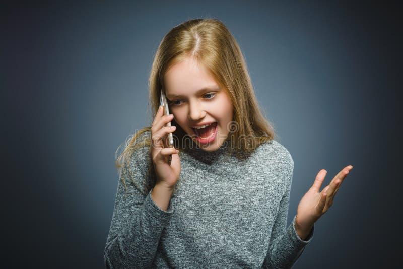 Menina bonito surpreendida com telefone celular Isolado no cinza imagens de stock