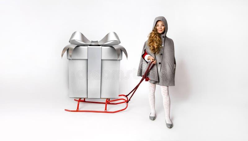 Menina bonito vestida no traje de Santa Claus que guarda um trenó imagens de stock