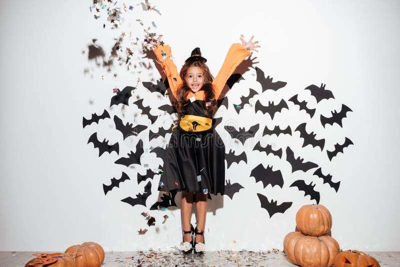 A menina bonito vestiu-se no traje do Dia das Bruxas que tem o divertimento imagem de stock