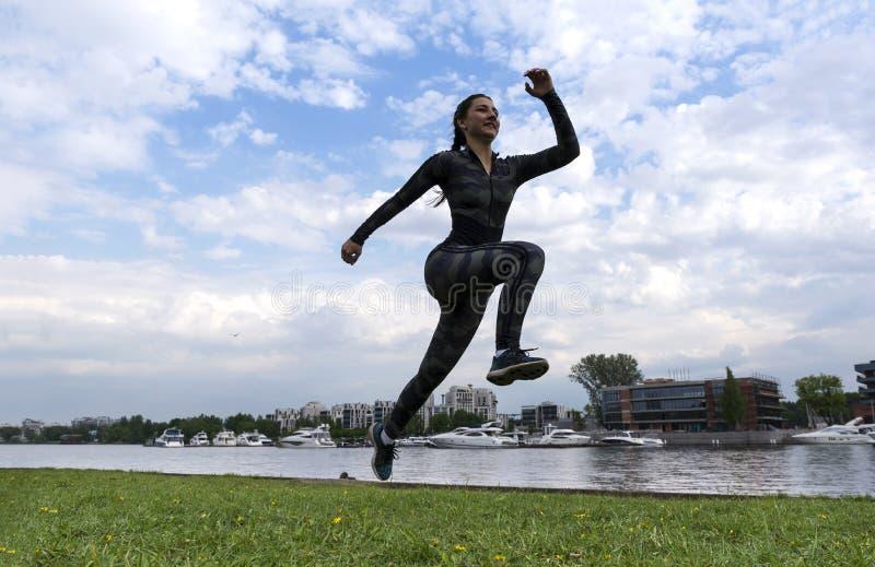1 menina branca na roupa dos esportes que corre em um parque no banco de rio contra o céu com nuvens, corredor fotos de stock