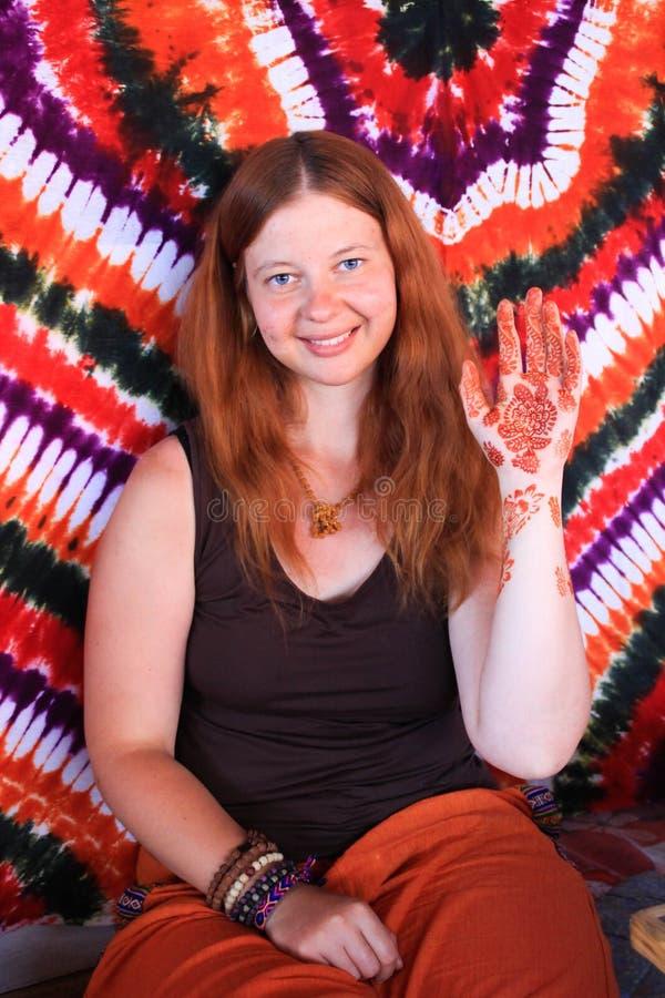 A menina branca nova bonita no fundo da mandala mostra uma mão com um teste padrão da hena foto de stock