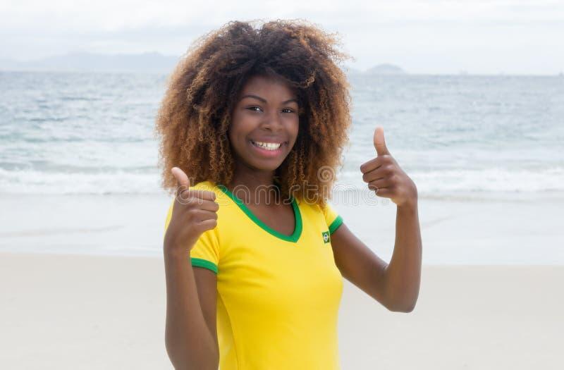 Menina brasileira de riso com o penteado louco que mostra ambos os polegares acima fotografia de stock