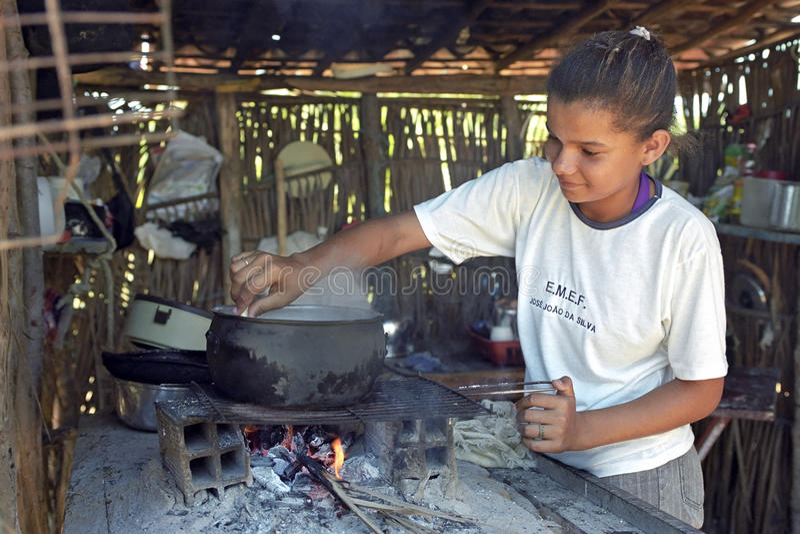 A menina brasileira está cozinhando em um fogo de madeira com lenha imagens de stock