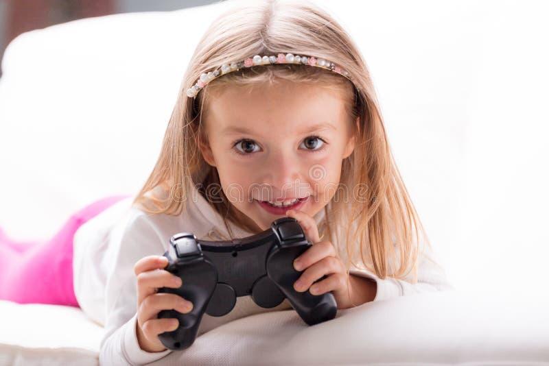 Menina brincalhão bonito com um controlador do jogo foto de stock royalty free