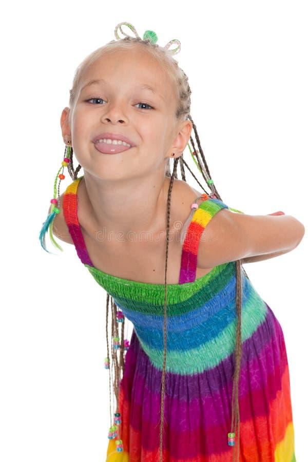 A menina brincalhão mostra a língua foto de stock
