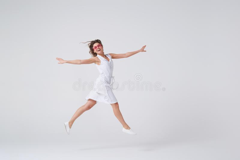 Menina brincalhão que gesticula e que sorri ao saltar contra o backgro imagens de stock
