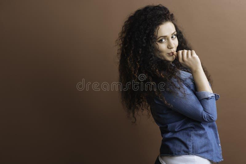 Menina brincalhão que põe seu dedo na boca foto de stock