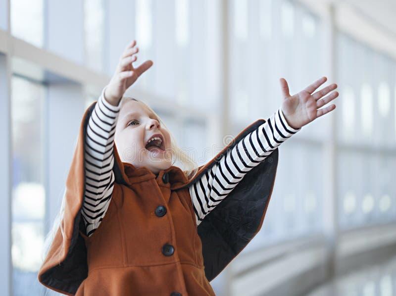 Menina brincalhão que veste a gritaria alaranjada do revestimento com alegria foto de stock royalty free