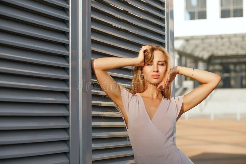 Menina bronzeada elegante no vestido na moda que levanta no fundo imagens de stock royalty free