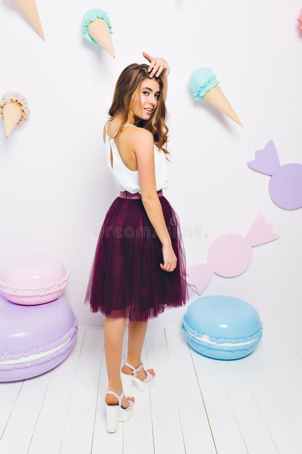 Menina bronzeada magro na saia violeta longa que olha sobre seu ombro que levanta no partido do tema e que toca no cabelo Complet fotografia de stock royalty free