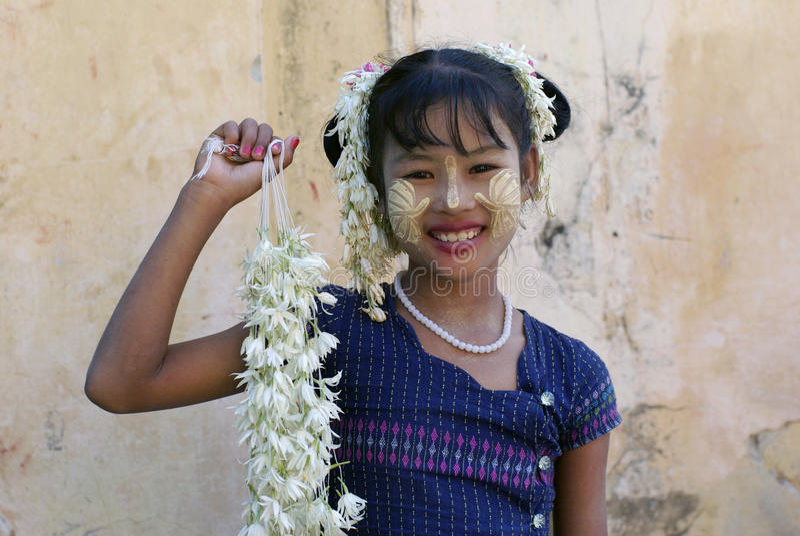 Menina burmese de sorriso não identificada com o thanaka tradicional em sua cara o 3 de janeiro de 2011 em Mandalay, Myanmar imagens de stock