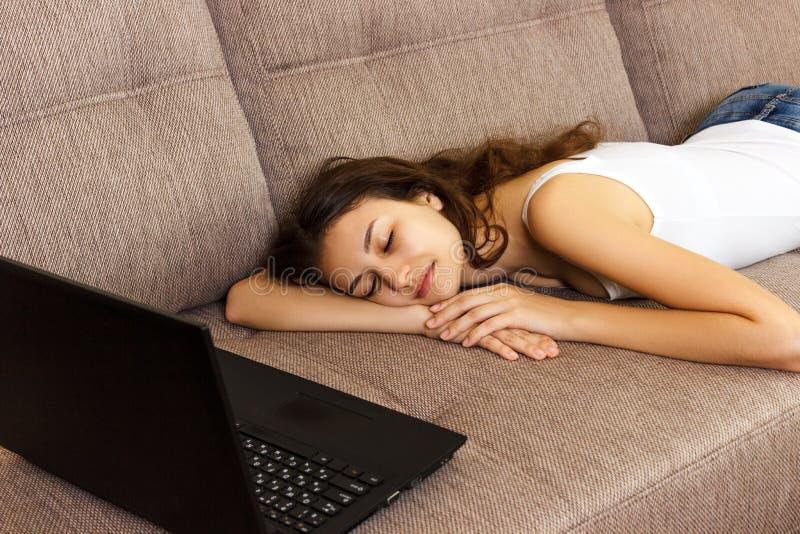 A menina caiu adormecido com um portátil no sofá Cansado e caiu adormecido imagem de stock