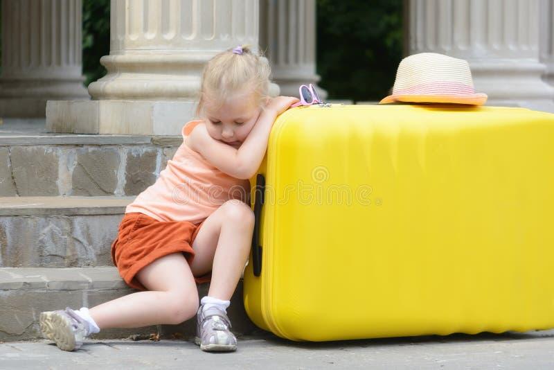 A menina caiu adormecido, inclinando seus cotovelos em uma mala de viagem amarela grande Retrato de uma menina bonita T fotos de stock