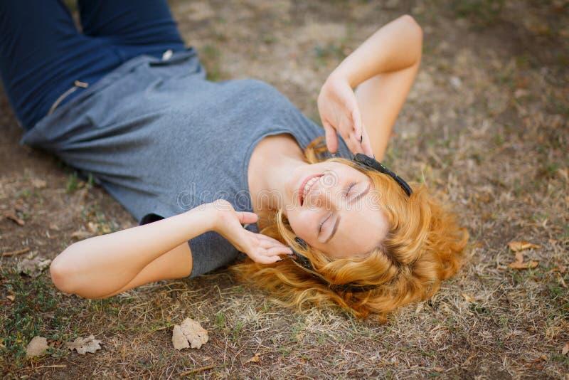 Menina calma do gengibre nos fones de ouvido que relaxam em um fundo da grama Conceito do tempo livre imagem de stock royalty free