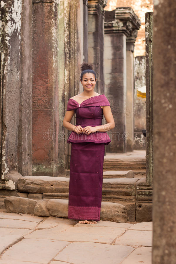Menina cambojana no vestido do Khmer que está no templo de Bayon na cidade de Angkor imagens de stock