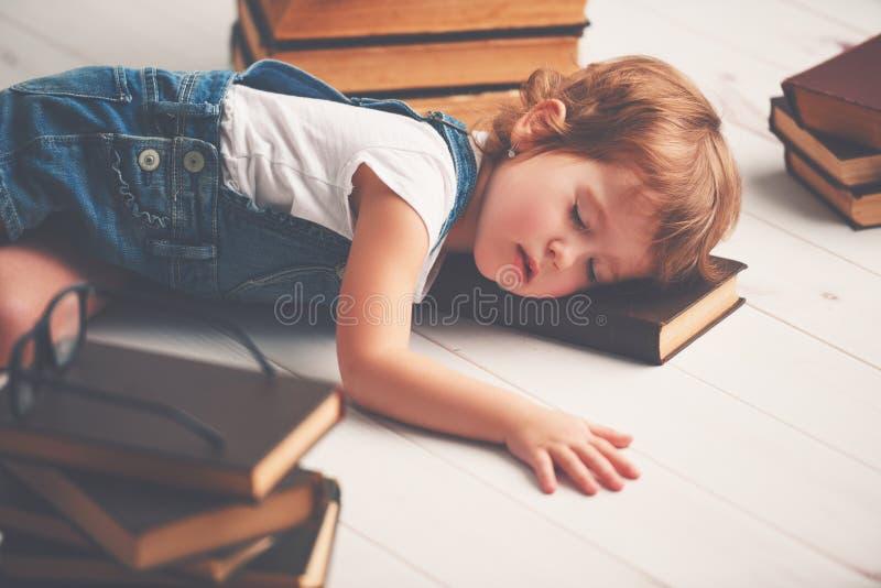 A menina cansado caiu adormecido para livros fotografia de stock royalty free