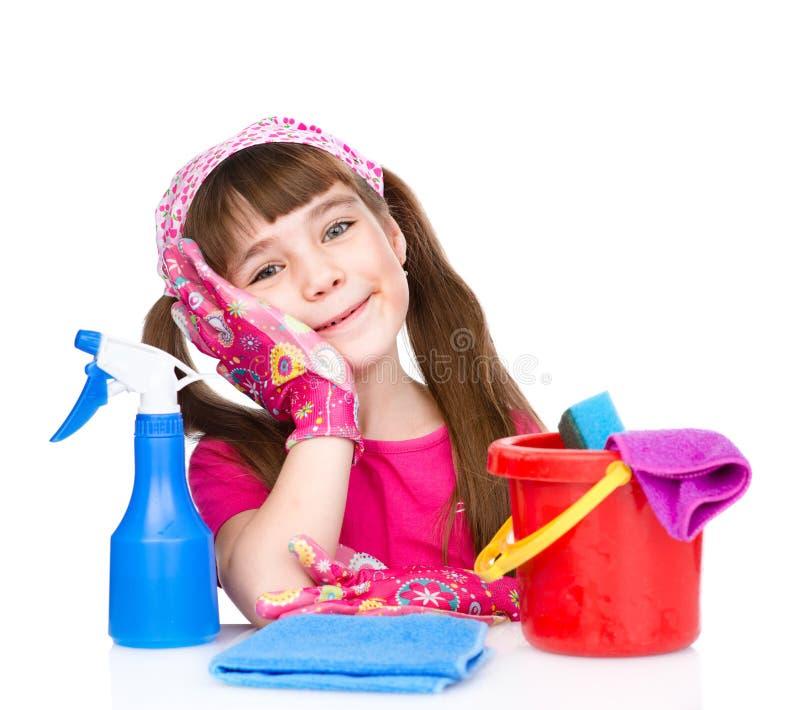 Menina cansado com equipamento para limpar a casa no branco foto de stock