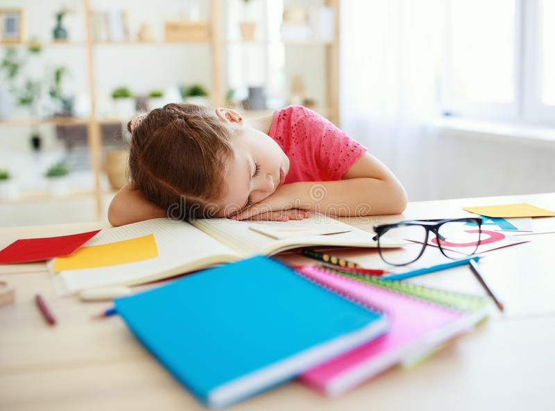 A menina cansado da crian?a caiu adormecido quando fez seus trabalhos de casa em casa fotos de stock royalty free