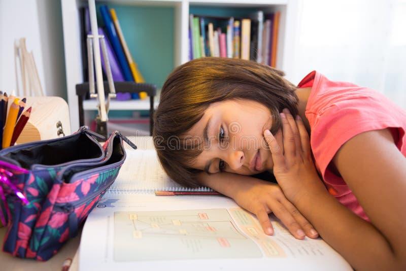 Menina cansado da escola que faz trabalhos de casa fotografia de stock royalty free