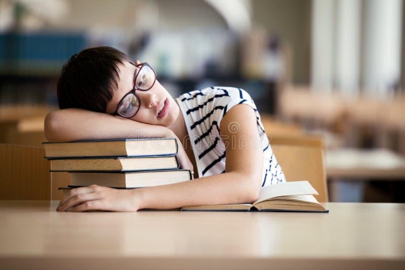 Menina cansado do estudante com vidros que dorme nos livros imagens de stock royalty free