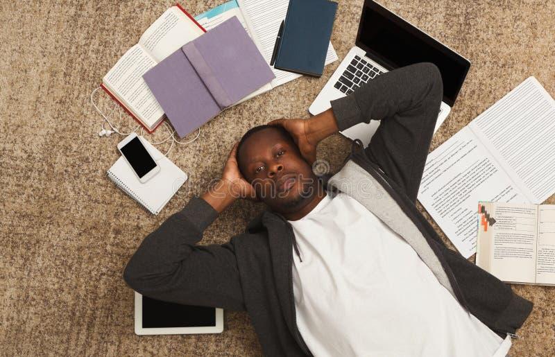 Menina cansado do estudante que encontra-se no assoalho com livros e dispositivos imagem de stock royalty free