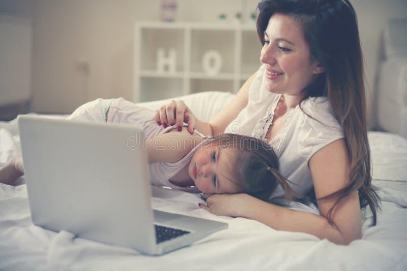 Menina cansado que encontra-se na cama com seu somethin de observação da mãe foto de stock