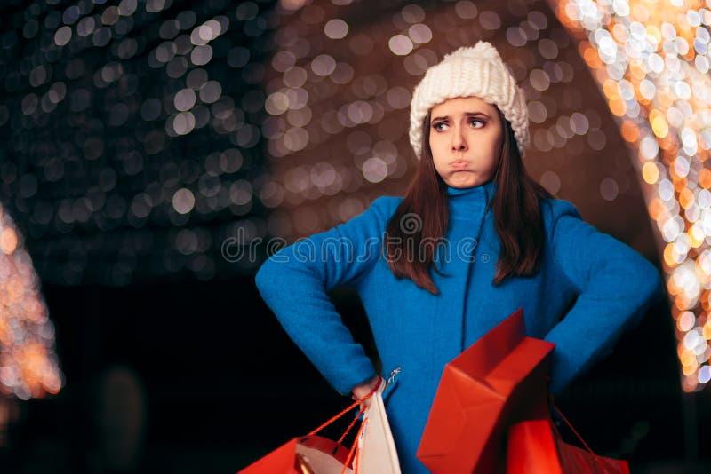 Menina cansado que guarda sacos de compras em luzes de Natal Décor imagem de stock