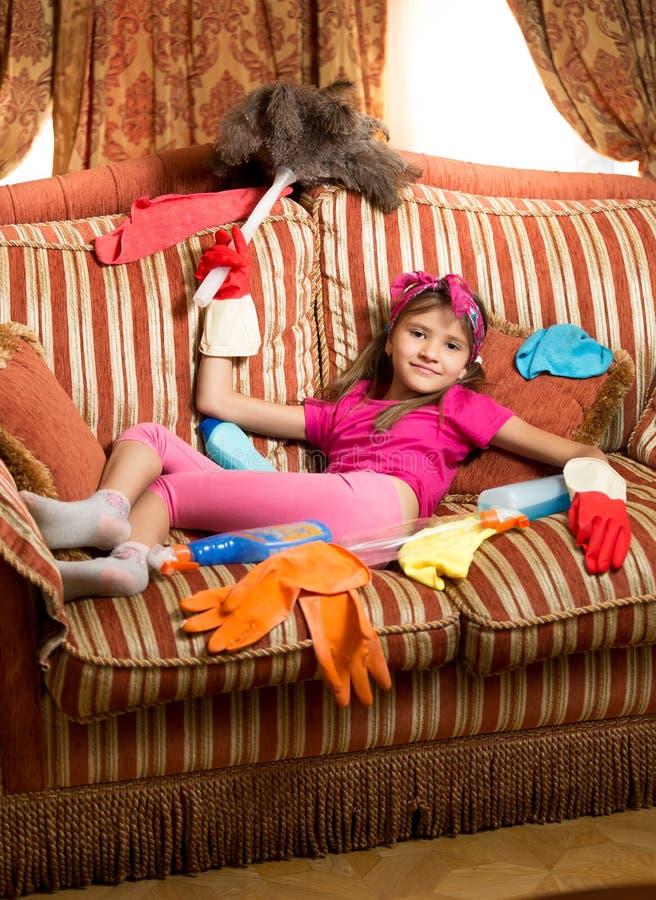 Menina cansado que relaxa no sofá após ter limpado a casa imagens de stock royalty free