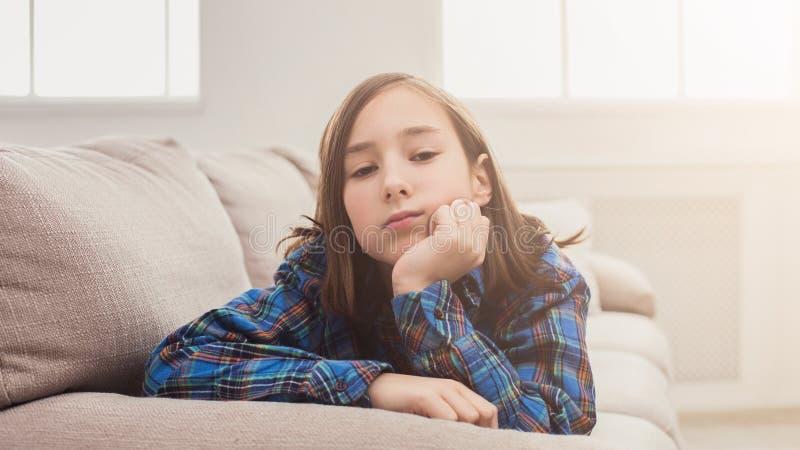 Menina cansado que senta-se no sofá em casa fotografia de stock royalty free