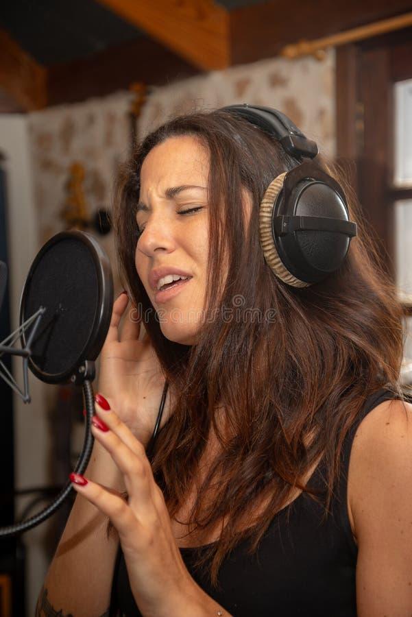 A menina canta no estúdio de gravação fotos de stock royalty free