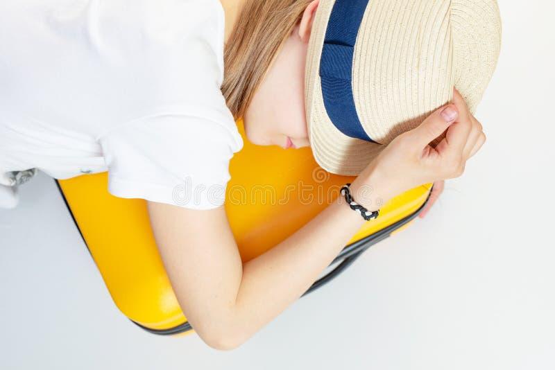 Menina caucasiana de chapéu está sobre uma mala, cansada de esperar Férias, acampamento de verão, viagem, viagem imagem de stock