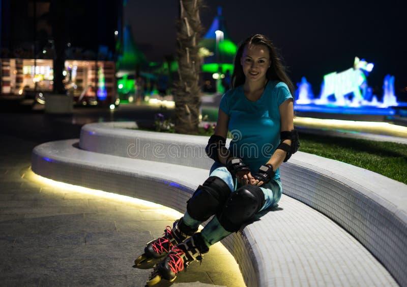 A menina caucasiano aprecia a patinagem de rolo na cidade da noite com luzes no bokeh fotografia de stock
