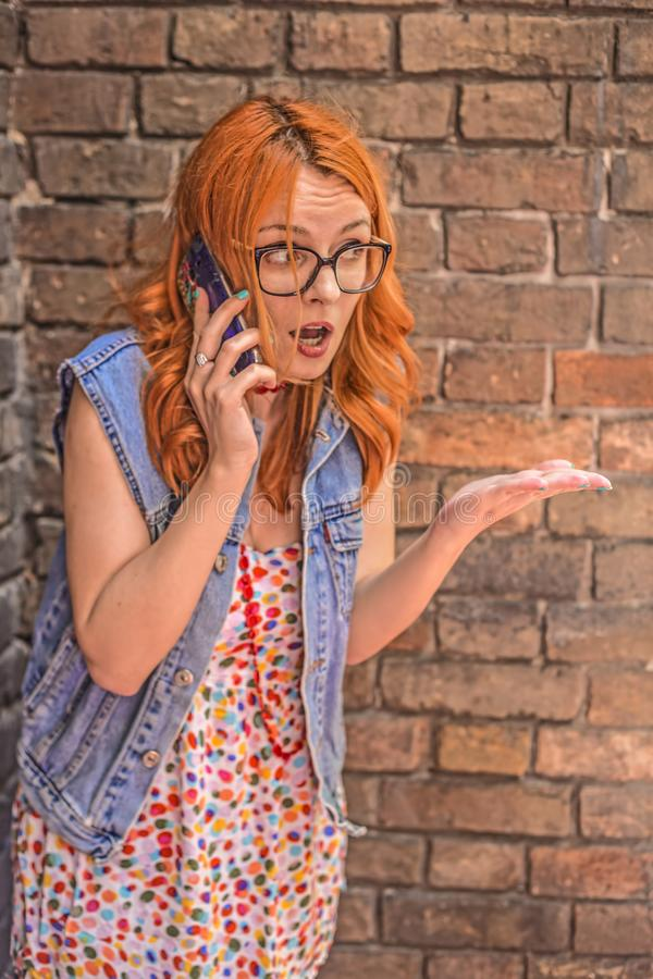 Menina caucasiano bonita do ruivo irritado e confuso que fala no telefone esperto fotos de stock royalty free