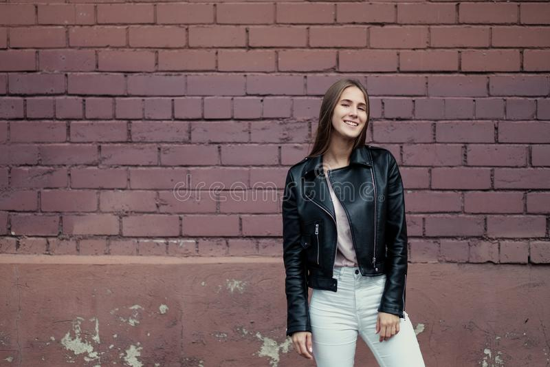 Menina caucasiano bonita nova que levanta em um casaco de cabedal preto em um fundo da parede de tijolo imagens de stock