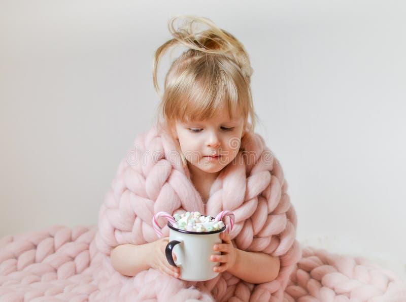 Menina caucasiano bonita pequena que guarda o copo com Natal de espera do chocolate quente e ano novo, pi pastel geral de lã do M foto de stock
