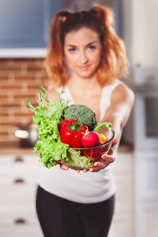 Menina caucasiano bonita que guarda a bacia de vidros com os ingredientes para a salada baixo-calórica dos vegetais na cozinha fotos de stock