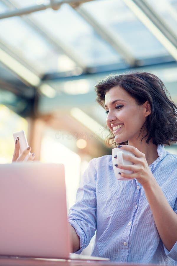 Menina caucasiano branca bonita de sorriso com o cabelo encaracolado preto que senta-se na barra e em usar da rua seu telefone foto de stock