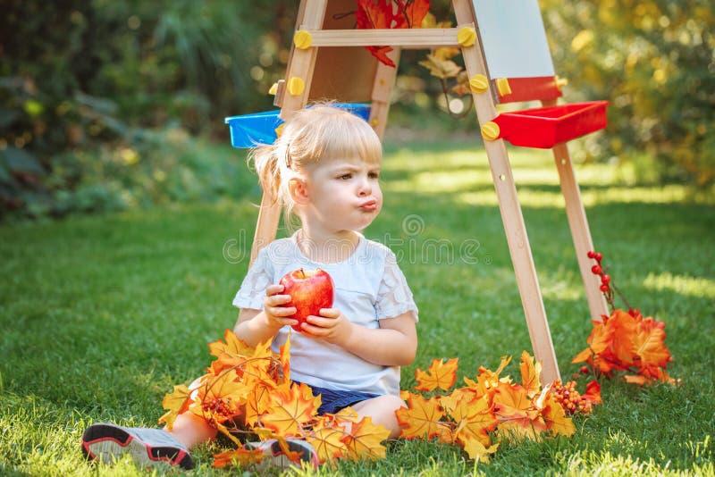 Menina caucasiano branca da criança da criança da criança que senta-se fora no parque do outono do verão tirando a armação que co foto de stock