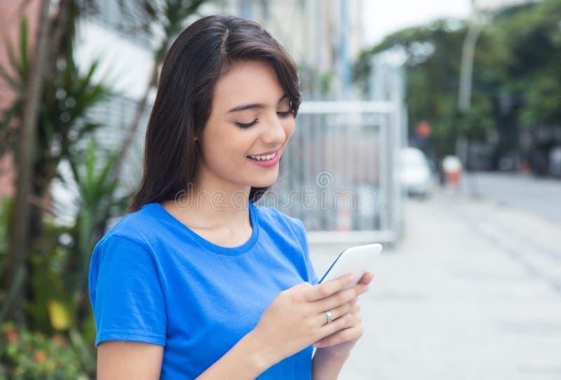 Menina caucasiano com camisa azul usando o wifi com telefone imagens de stock royalty free