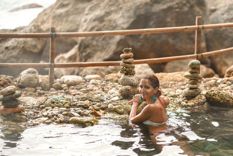 A menina caucasiano com um sorriso banha-se na associação natural morna foto de stock