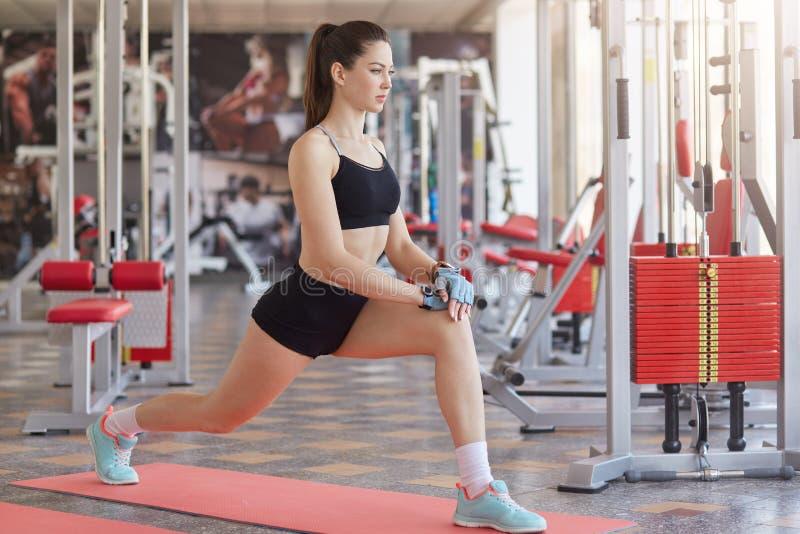 Menina caucasiano da aptidão que faz esticando o exercício no assoalho no gym Tiro completo do comprimento da moça no centro d fotografia de stock royalty free