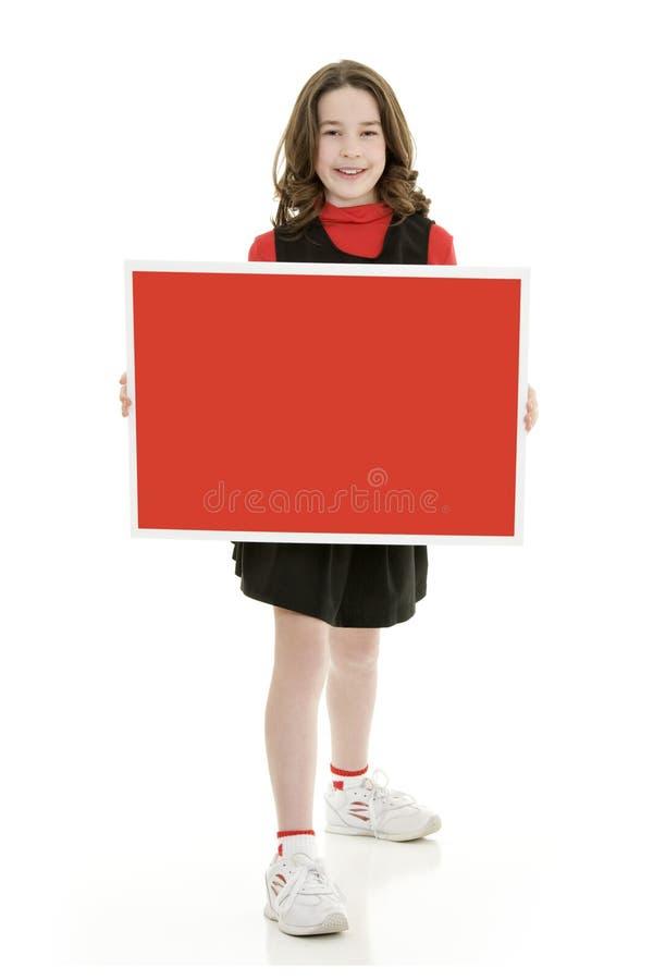 Menina caucasiano da criança de dez anos vestida como um equipamento vermelho do líder da claque imagens de stock