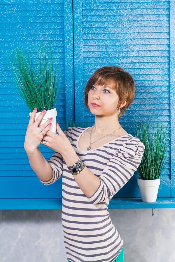 Menina caucasiano de cabelos curtos consideravelmente nova que guarda o pott? planta de d perto da janela azul Tiro do estúdio, c foto de stock royalty free