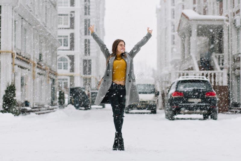 Menina caucasiano de relaxamento que levanta com mãos acima sob a queda de neve no fundo urbano Foto completo exterior de conside imagens de stock royalty free