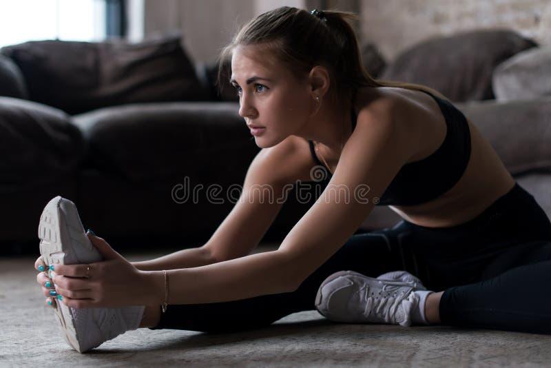 Menina caucasiano desportiva magro que senta-se no assoalho que faz esticando o exercício dentro imagem de stock