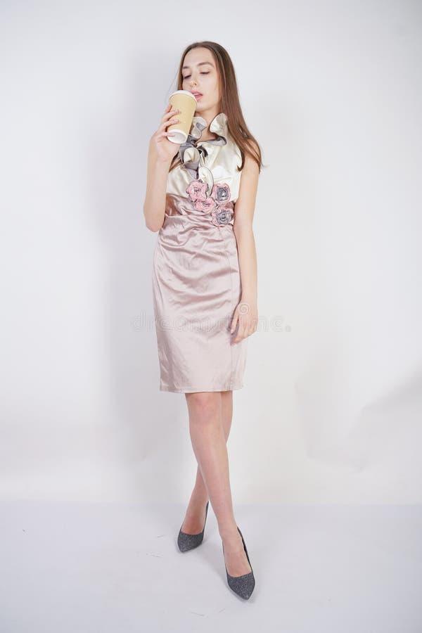 Menina caucasiano do adolescente bonito no vestido de nivelamento elegante com o copo de café de papel no fundo branco no estúd fotografia de stock
